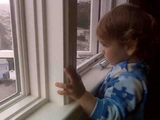 Saying goodbye, my nephew waves at the window.