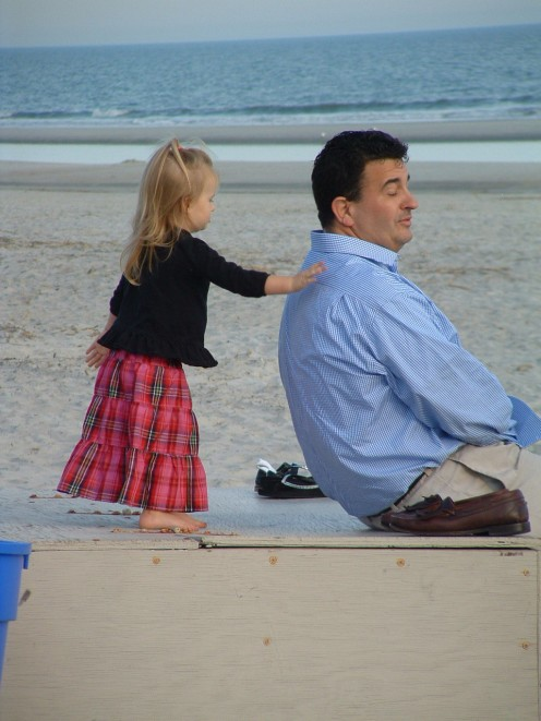The beach is a magical place for families to spend time together. This beautiful little girl is giving her Daddy a blissful back massage.