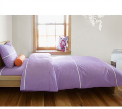 This bed made with a lilac and white striped duvet and an orange accent pillow create a fun yet serene atmosphere in this young girl's room.