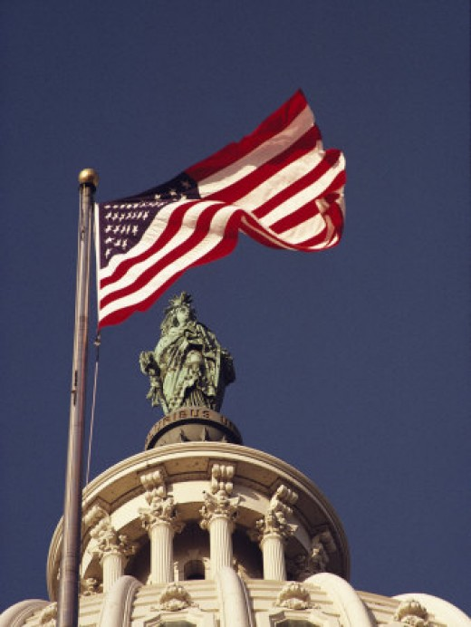 An American Flag and the Statue of Freedom Atop the Capitol Dome