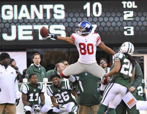 Photo credit: David Pokress | Victor Cruz of the Giants celebrates a long completion in the third quarter in front of the Jets bench. (Dec. 24, 2011)