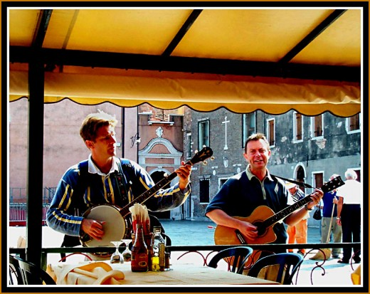 """that means """"two."""" One plays a banjo. The other a guitar. They also look happy. These guys, like our friend in the top photo, enjoyed sharing their talents with people. What a way to be remembered."""
