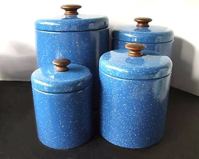 This old-fashioned blue enamelware canister set is metal with wooden knobs.