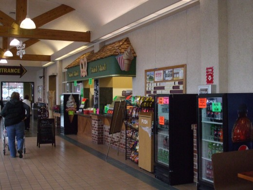 A snack shop, vending machines, and other small sales areas line a 20 foot wide hall outside the supermarket.