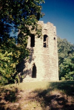 """From the road you can barely see below the tower in the earlier photo. Meaning: """"Oh, goodie. Another mile and a half of deep woods and rutted road before we're back in civilization..."""""""