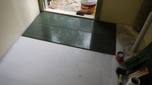 8 These tiles are 300mm x 600mm. Being quite large, you can't have much of a slope on the floor, and the surface needs to be flat. Lay out the tiles and check out where they lie in the room. Use the scraper on any high spots, reapply membrane.