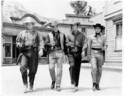 (FROM LEFT) HOSS, BEN, ADAM, AND JOE WALK DOWN MAIN STREET SOMEWHERE IN NEVADA WITH GUNS IN HAND. FUNNY, THIS IS A 'GHOST TOWN.'