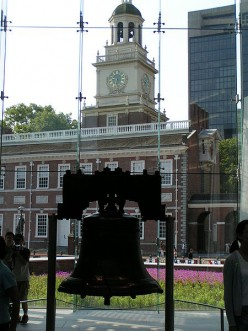 The Liberty Bell hangs in the Liberty Bell Center, with Independence Hall visible through the glass.
