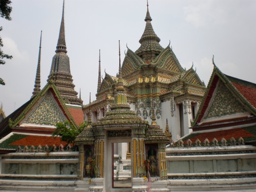 Set of chapels and stupas painstakingly decorated in different patterns and colors. Wat Pho Buddhist Complex in Bangkok, Thailand.