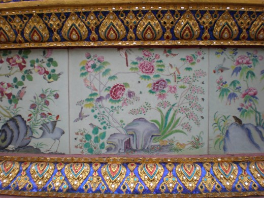 Delicately painted mosaics, such as this one, are part of the Buddhist decorating style. Wat Phra Kaew Buddist Temple in Bangkok, Thailand.