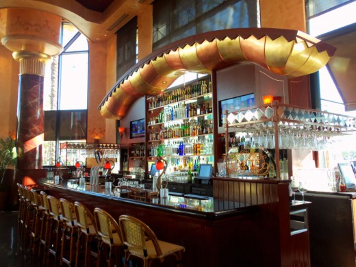 "- Photo of ""The Cheesecake Factory Bar"" - Close up image capturing a side angle perspective with wine glass rack to the right and imposing synthetic marble column to the left creating an impressive visual setting and classic ""Movie Set"" experience -"