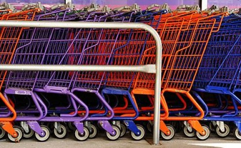 Colorful shopping carts all nestled neatly in a cart corral