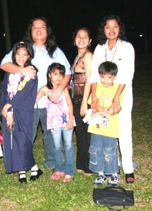 My son and his children, the eldest girl and the boy-girl twins; this picture was taken when they were still living near my home in 2004. Beside me is my daughter when she was still single.