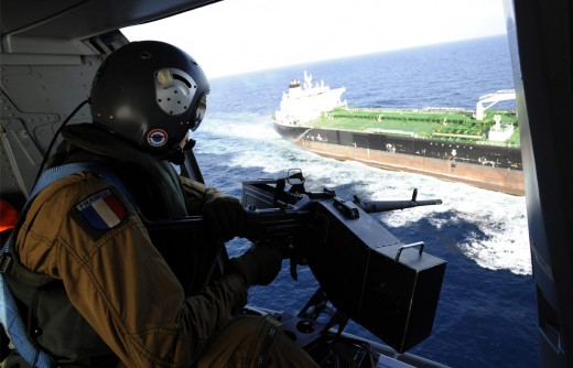 French door gunner on a Panther helicopter watches over a commercial ship as it enters the Gulf of Aden