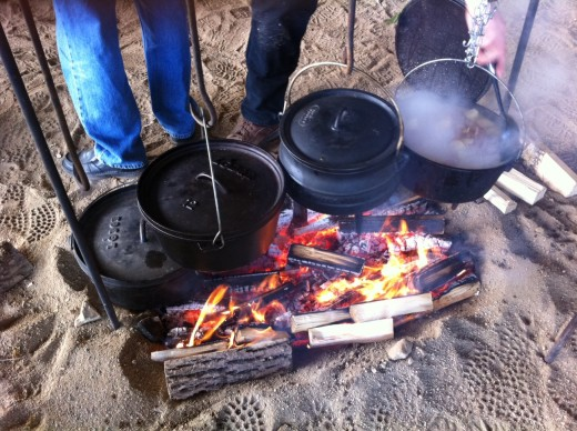 Four dutch ovens at a farm hand cookout.