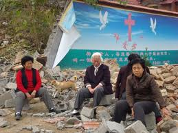 Persecuted believers in China sit in the rubble of their demolished Church.
