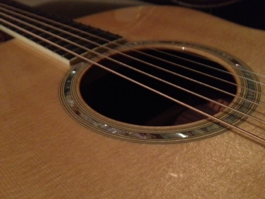 A gorgeous inlay around an acoustic guitar soundhole.