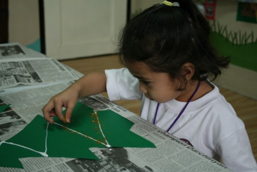 """""""This is fun!"""" Our three year old student is engrossed in sprinkling the glitters."""