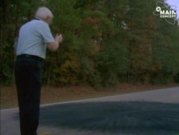 A photograph of an investigator investigating a scorch mark in the road where Cash and Landrum said the UFO hovered.