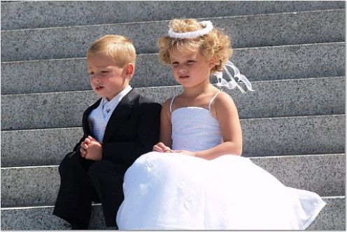 A flower girl and ring bearer patiently waiting to take part in wedding photographs
