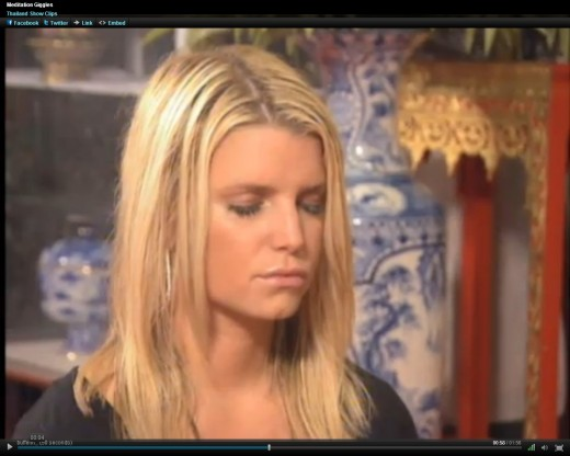Jessica Simpson laughs in front of monk while meditating.