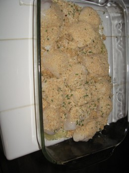 Scallops in baking dish with bread crumb mixture sprinkled and ready for oven.