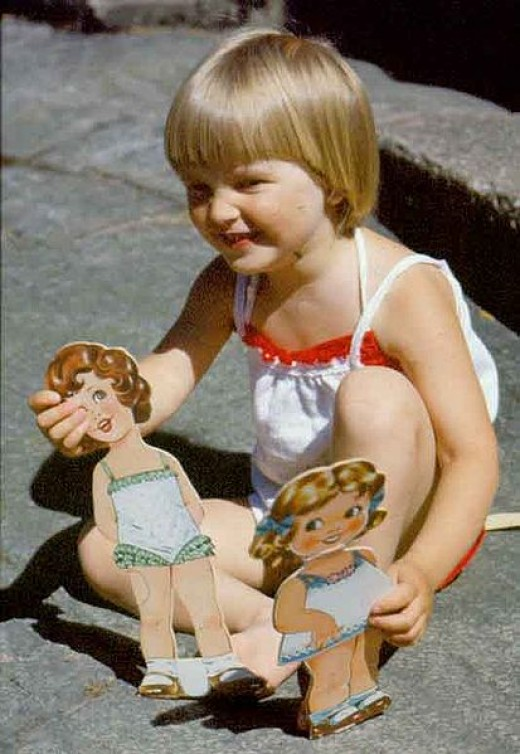 Little girl playing with paper dolls, always fun they could provide hours of imaginative play!