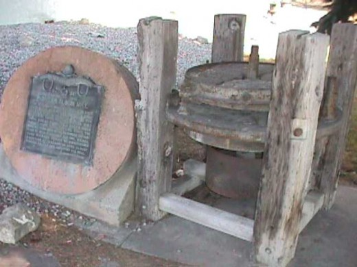 An historical marker for the grindstones and mechanism of the area's first flour mill.