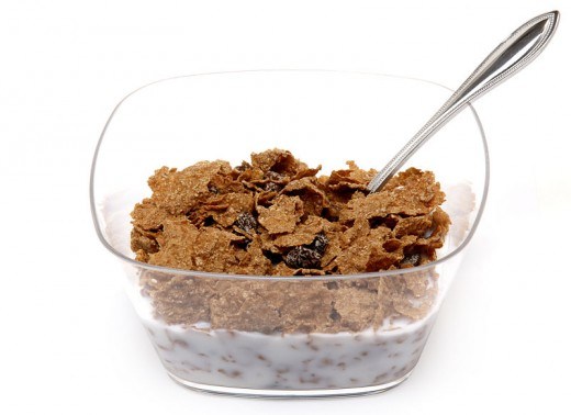 A bowl of Raisin Bran cereal shown in a clear plastic bowl and low-fat milk