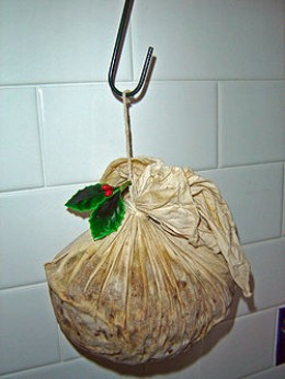 Christmas pudding drying out on hook in order to enhance the flavour. This pudding has been prepared with a traditional cloth rather than a basin.