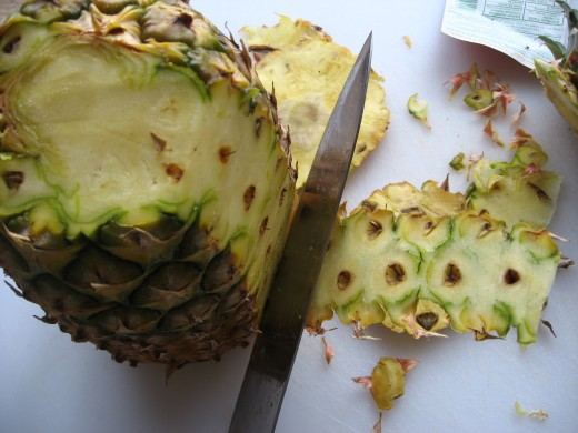 Place the pineapple upright and start removing the skin. Notice the eyes and less waste.