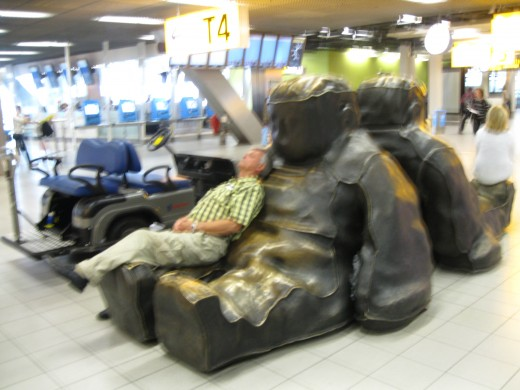 Amsterdam Airport Schiphol - resting on a sculpture.  Not very comfortable but my wife wanted a picture.