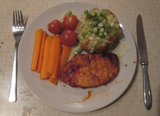 A complete meal: Jacket potato with BBQ chicken, and side salas of carrots and tomatos