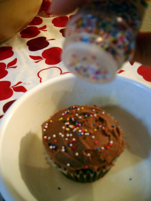 Set the cupcake in a small bowl or dish to keep the sprinkles from rolling all over the place!