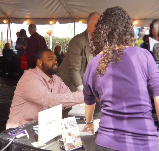 "Michael Oher, the Baltimore Ravens football player whose story was made into a movie called The Blind Side, signed copies of his book, ""I Beat the Odds: From Homelessness to The Blind Side and Beyond."""