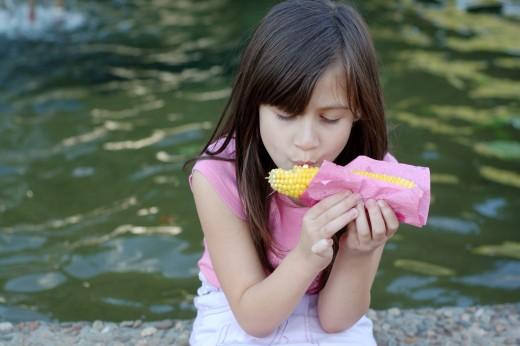 GIRL EATING CORN by Dimistudio Litle girl eating corn on the cob