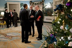 President Obama (left) listens to an intelligent man who is talking to him about an upcoming political conference that Mr. Obama needs to attend.