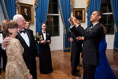 President Obama takes time out from shaking hands of important people to snap their photo. What a treat. Having the most-powerful man in the free world snap your photo.