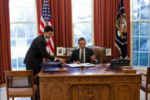 President Obama (center) at work in the Oval Office signing an important document that will undoubtably change our lives in some way.