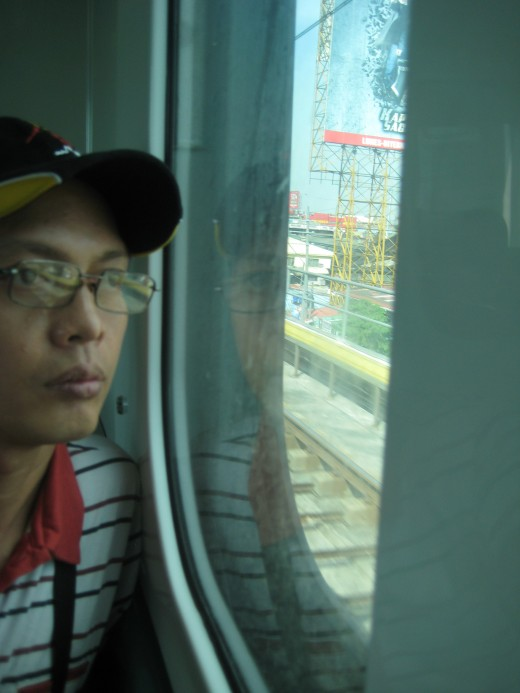 Travel Man looking outside the porthole of LRT train
