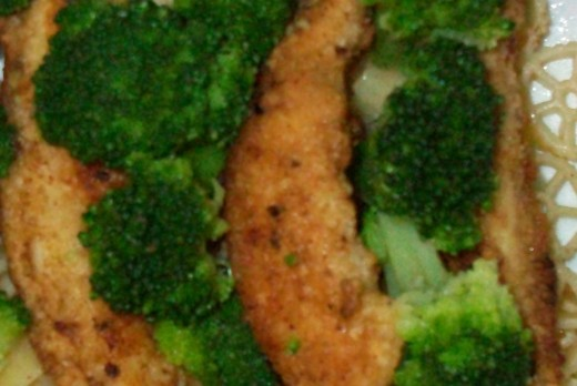 Chicken fingers with broccoli served over mini wagon wheel pasta