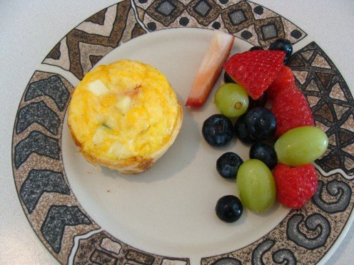 Egg cup served with a side of fresh fruit.