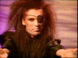 "Capture from the ""You Spin Me Round (Like a Record)"" music video."