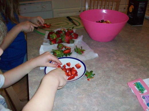 Younger kids can use table knives or even plastic knives on soft fruit like strawberries and bananas.