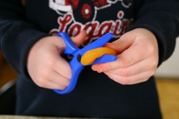 Use children's safety scissors to cut the dried fruit.