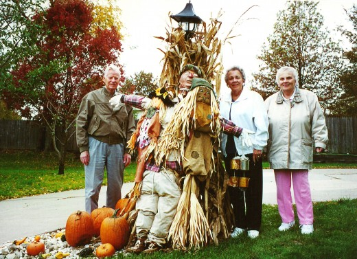 My uncle, mother & aunt standing by a fall decoration.