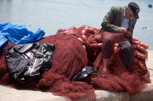 "A fisherman repairing his fishing nets in Essaouira, Morocco. -- ""Good things come to those who bait."" ~Author Unknown"