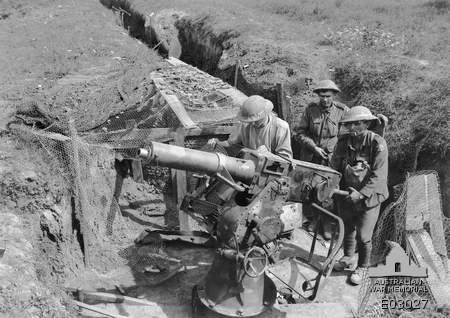 Australian forces standing by a captured German gun point