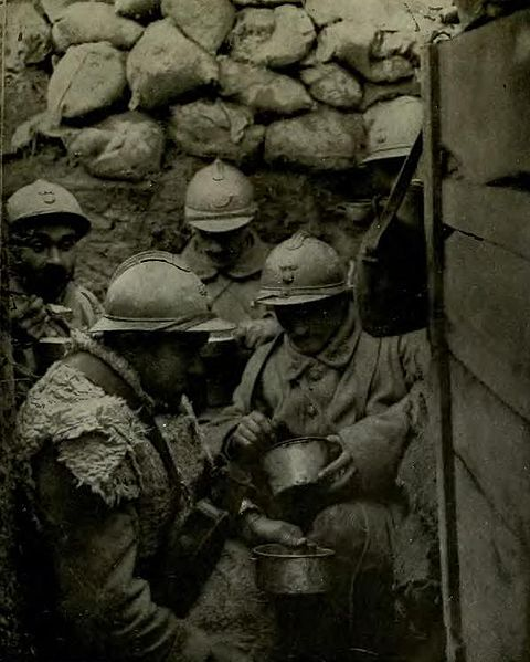 French soldiers, eating in mud covered clothes