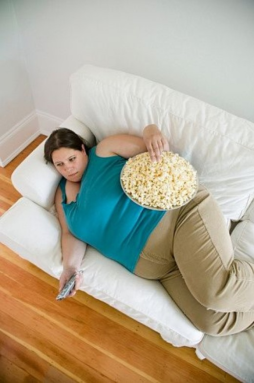 A fat woman watching TV while eating.